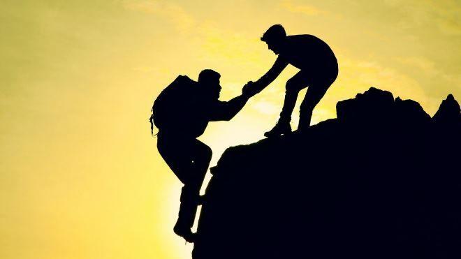 Мужчина помогает мужчине взобраться на гору