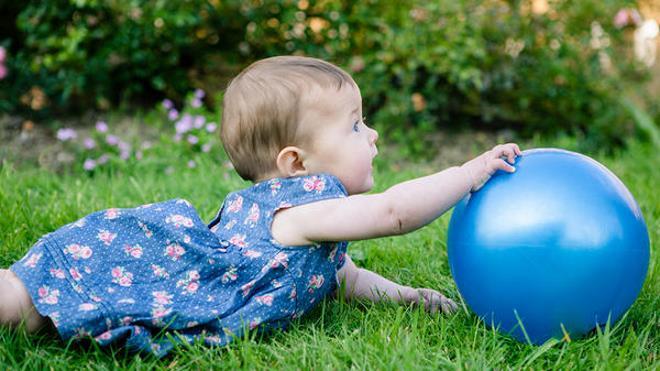 Малышка тянется к мячу